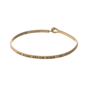 "Gold tone, brass bangle bracelet stamped with ""Aim High, Dream Big."""