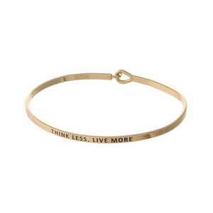 "Gold tone, brass bangle bracelet stamped with ""Think Less, Live More."""