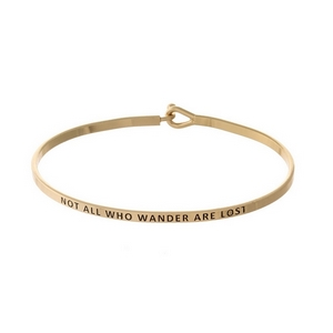 """Gold tone, brass bangle bracelet stamped with """"Not All Who Wander Are Lost."""""""