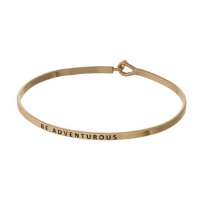 "Gold tone, brass bangle bracelet stamped with ""Be Adventurous."""