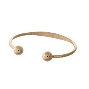 Gold tone cuff bracelet.