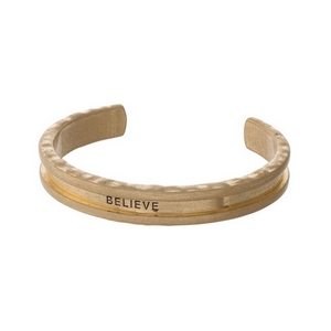 "Gold tone cuff bracelet stamped with ""Believe"" and used for holding your hair tie."