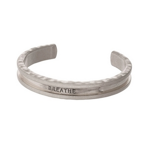 """Silver tone cuff bracelet stamped with """"Breathe"""" and used for holding your hair tie."""