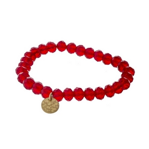 Red faceted bead stretch bracelet with a hammered gold tone circle charm.