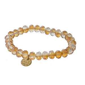 Light topaz faceted bead stretch bracelet with a hammered gold tone circle charm.