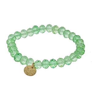 Light green faceted bead stretch bracelet with a hammered gold tone circle charm.
