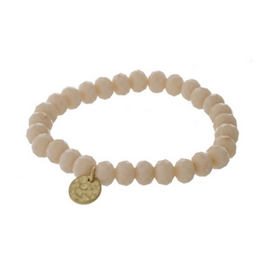 Ivory faceted bead stretch bracelet with a hammered gold tone circle charm.