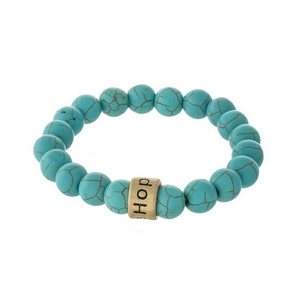 """Turquoise, natural stone beaded stretch bracelet with a gold tone bead, stamped with """"Hope."""""""