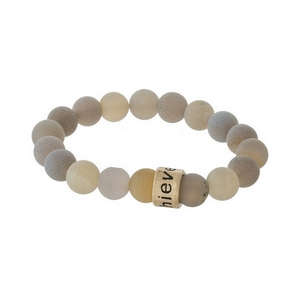 """Matte gray, natural stone beaded stretch bracelet with a gold tone bead, stamped with """"Achieve."""""""