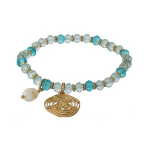 Turquoise and mint green beaded stretch bracelet featuring a gold tone sand dollar charm.