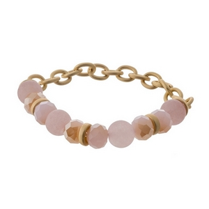 Matte gold tone stretch bracelet displaying pink and peach natural stone beads.