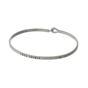 "Silver tone, brass bangle bracelet stamped with ""Free Spirit""."