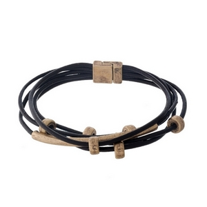 Brown leather cord bracelet with gold tone accents and a magnetic closure.