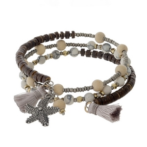 White, tan, and brown beaded coil bracelet with a silver tone starfish charm and gray tassel accents.