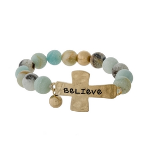 "Amazonite beaded stretch bracelet with a gold tone cross, stamped with ""Believe."""