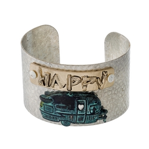 "Hammered silver tone cuff bracelet with ""Happy Camper"" in two tone. Cuff measures approximately 1.5"" in width."