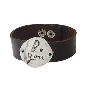 "Brown faux leather snap bracelet with a silver tone focal stamped with ""Be You."" Approximately 1"" in width."