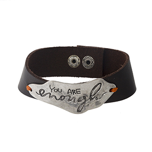 "Brown faux leather snap bracelet with a silver tone focal stamped with ""You Are Enough."" Approximately 1"" in width."