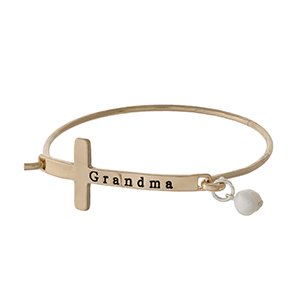 "Gold tone bangle bracelet with a cross focal, stamped with ""Grandma"" and accented with a pearl bead."