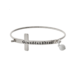 "Silver tone bangle bracelet with a cross focal, stamped with ""Granddaughter"" and accented with a pearl bead."