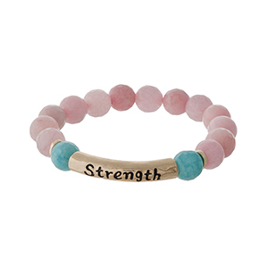 "Pink natural stone beaded stretch bracelet with a gold tone bar stamped with ""Strength."""