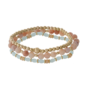 Three piece stretch bracelet set featuring gold tone, peach natural stone, and light blue faceted beads.