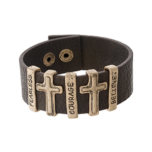 "Brown faux leather snap bracelet with gold tone crosses and bars stamped with ""Fearless, Courage, Believe."" Approximately 1"" in width."
