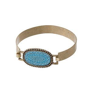 Matte gold tone bangle with a turquoise pave rhinestone oval focal.