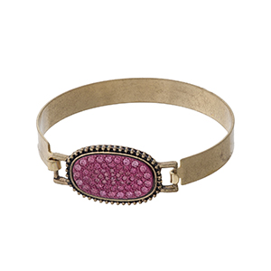Matte gold tone bangle with a pink pave rhinestone oval focal.