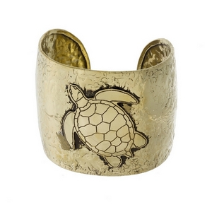 "Gold tone, handmade brass cuff bracelet with a turtle focal. Approximately 2"" in width."