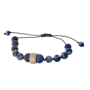 Brown cord bracelet with sodalite natural stone beads, a gold tone bead accents and a pull-tie closure.