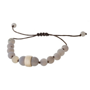 Brown cord bracelet with gray natural stone beads, a gold tone bead accents and a pull-tie closure.