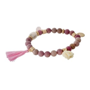 Mauve natural stone beaded stretch bracelet with a pink tassel, gold tone accents and an elephant charm.