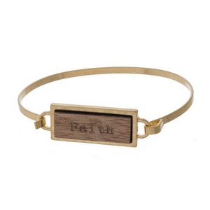 "Gold tone bangle bracelet featuring a wooden focal stamped with ""Faith."""