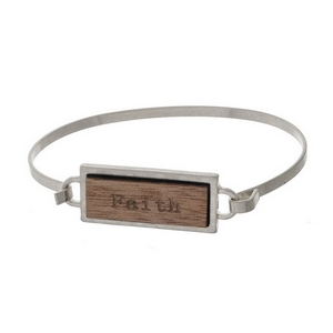 "Silver tone bangle bracelet featuring a wooden focal stamped with ""Faith."""