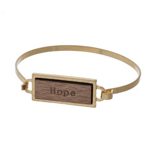 "Gold tone bangle bracelet featuring a wooden focal stamped with ""Hope."""