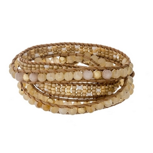 Brown cord wrap bracelet featuring beige faceted and natural stone beads, gold tone accents and a button closure.