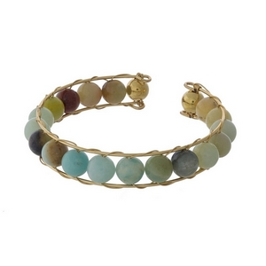 Gold tone cuff bracelet featuring wire wrapped amazonite beads.