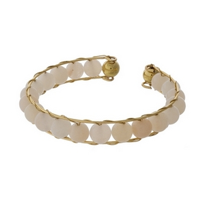 Gold tone cuff bracelet featuring wire wrapped ivory beads.