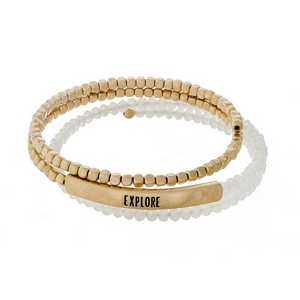 "White opal and gold tone beaded coil bracelet featuring a bar stamped with ""Explore."""