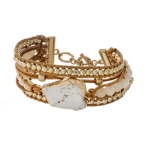 Brown leather cord bracelet featuring an ivory stone, ivory beads, and a gold tone toggle closure.
