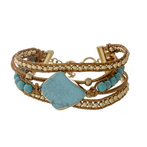 Brown leather cord bracelet featuring a turquoise stone, turquoise beads, and a toggle closure.