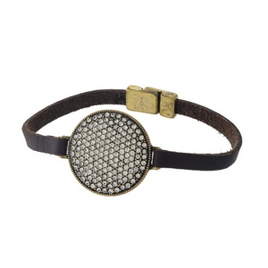 Brown leather bracelet with a burnished gold tone and clear rhinestone circle, and a magnetic closure.