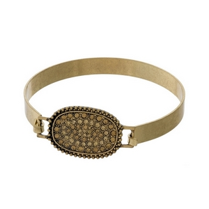 Gold tone hinged bangle bracelet with a topaz pave rhinestone oval focal.