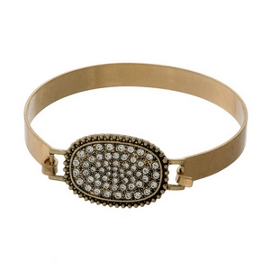 Gold tone hinged bangle bracelet with a clear pave rhinestone oval focal.