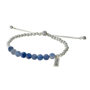 "Silver tone beaded pull-tie bracelet featuring blue beads and a bar charm stamped with ""Peace."""