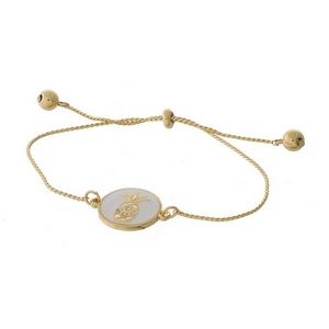 "Dainty gold tone pull-tie bracelet with a pineapple on one side and the other side is stamped with ""Friends are forever."""