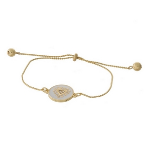 "Dainty gold tone pull-tie bracelet with a heart on one side and the other side is stamped with ""I'll always love you."""