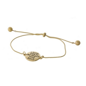 "Dainty gold tone pull-tie bracelet with a moon on one side and the other side is stamped with ""I love you to the moon and back."""