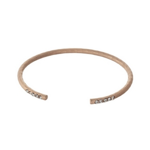 Hammered rose gold tone cuff bracelet with clear rhinestone accents.